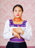 Young woman wearing traditional andean dress, facing camera doing sign language word for son Stock Photo
