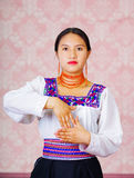 Young woman wearing traditional andean dress, facing camera doing sign language word for study Royalty Free Stock Images