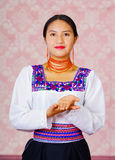 Young woman wearing traditional andean dress, facing camera doing sign language word for thank you.  stock photo