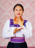 Young woman wearing traditional andean dress, facing camera doing sign language word for thank you.  royalty free stock images