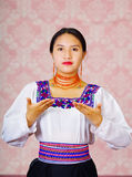 Young woman wearing traditional andean dress, facing camera doing sign language word for trade Stock Images