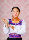 Young woman wearing traditional andean dress, facing camera doing sign language word for wait Stock Photography