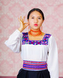 Young woman wearing traditional andean dress, facing camera doing sign language word for woman Stock Photo