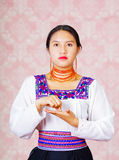 Young woman wearing traditional andean dress, facing camera doing sign language word for writing Royalty Free Stock Photography