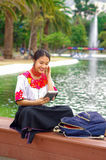 Young woman wearing traditional andean skirt and blouse with matching red necklace, sitting on bench next to lake in Royalty Free Stock Photo