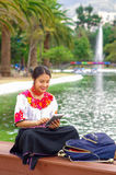 Young woman wearing traditional andean skirt and blouse with matching red necklace, sitting on bench next to lake in Royalty Free Stock Photos
