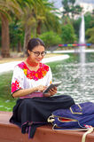 Young woman wearing traditional andean skirt and blouse with matching red necklace, sitting on bench next to lake in Royalty Free Stock Image
