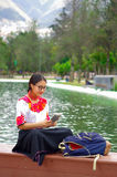 Young woman wearing traditional andean skirt and blouse with matching red necklace, sitting on bench next to lake in Stock Photos