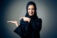 Young Woman Wearing Traditional Arabic Clothing. Studio shot of young woman wearing traditional arabic clothing. she`s holding her hand to the side so you can Royalty Free Stock Photos