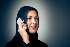 Young Woman Wearing Traditional Arabic Clothing. Studio shot of young woman wearing traditional arabic clothing, talking on the phone Stock Photo