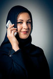 Young Woman Wearing Traditional Arabic Clothing. Studio shot of young woman wearing traditional arabic clothing, talking on the phone Royalty Free Stock Photo