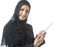 Young Woman Wearing Traditional Arabic Clothing. Studio shot of young woman wearing traditional arabic clothing, using digital tablet Stock Image
