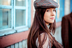 Young woman wearing tweed flat cap old fashioned portrait brown clothes. Royalty Free Stock Photo