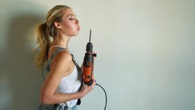 Young woman wearing uniform working on construction site, playing with electric drill like a gun stock footage