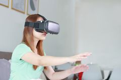 Young woman wearing virtual reality glasses at home. Royalty Free Stock Photography