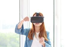 Young woman wearing virtual reality glasses at home. Stock Images
