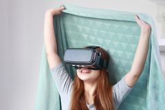Young woman wearing virtual reality glasses at home. Stock Photography