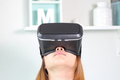 Young woman wearing virtual reality glasses at home. Stock Photos