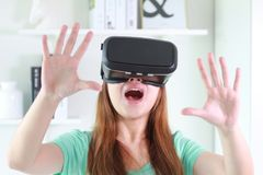 Young woman wearing virtual reality glasses at home. Royalty Free Stock Photo