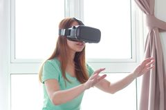 Young woman wearing virtual reality glasses at home royalty free stock image