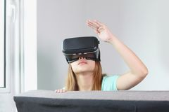 Young woman wearing virtual reality glasses at home stock images