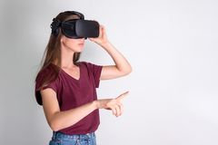 Young woman wearing virtual reality goggles headset, vr box. Connection, technology, new generation, progress concept. Girl trying. To touch objects in virtual royalty free stock image