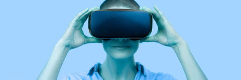Young woman in her 30s using virtual reality goggles. Woman wearing VR headset isolated over blue banner. VR experience. stock images