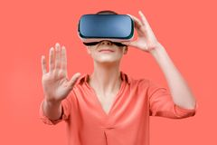 Young woman in her 30s using virtual reality goggles. Woman wearing VR headset  over coral background. VR experience. Young woman wearing virtual reality royalty free stock images