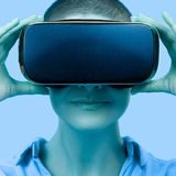 Young woman wearing virtual reality goggles. Woman wearing VR glasses over blue background. VR experience concept, close up. stock images
