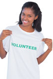 Young woman wearing volunteer tshirt and pointing to it