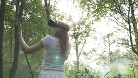 Young woman wearing VR headset in the forest experiencing augmented virtual reality -. Young woman wearing VR headset in the forest experiencing augmented stock video footage