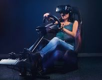 Young woman wearing VR headset having fun while driving on car racing simulator cockpit with seat and wheel. Woman wearing VR headset having fun while driving royalty free stock image