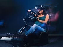 Young woman wearing VR headset having fun while driving on car racing simulator cockpit with seat and wheel. Woman wearing VR headset having fun while driving stock photo
