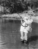 Young woman wearing waders holding a fishing rod. (All persons depicted are no longer living and no estate exists. Supplier grants that there will be no model Royalty Free Stock Images