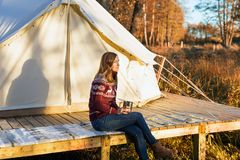 Young woman wearing warm jersey drinking cofee while sitting near a camping tent. In the autumn morning at the forest stock image