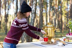 Young woman wearing warm jersey pouring some tea using vintage samovar at the forest. Russian picnic concept royalty free stock photos