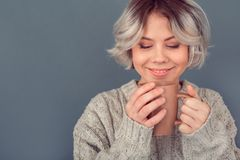 Young woman in a woolen sweater on grey wall winter concept hot coffee. Young woman wearing warm woolen winter sweater studio drinking hot coffee thinking about stock photos
