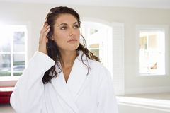 Young woman wearing white bath robe, standing indoors Royalty Free Stock Images