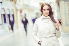 Young woman, wearing white coat, with long hair Royalty Free Stock Image