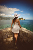 Young woman wearing white hat looking at far away island at sea Stock Photography