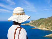 Young woman wearing a white hat looking at the sea. Shot taken from behind. Rocky coast, blue sea and sky in the background Stock Photography