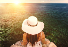 Young woman wearing white hat looking at sunset over the sea Stock Photography