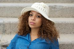 Young woman wearing white hat sitting on stairs outdoors Royalty Free Stock Image
