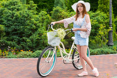 Young woman wearing a white hat standing near her bicycle Royalty Free Stock Images