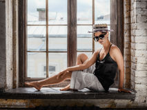 Young woman wearing white shorts, black top, hat and sunglasses. Sitting on windowsill. Retro style Royalty Free Stock Photos