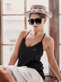 Young woman wearing white shorts, black top, hat and sunglasses. Sitting on windowsill. Retro style Stock Photos
