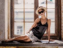 Young woman wearing white shorts, black top, hat and sunglasses. Sitting on windowsill. Retro style Royalty Free Stock Photo