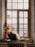 Young woman wearing white shorts, black top, hat and sunglasses. Sitting on windowsill. Retro style Royalty Free Stock Images