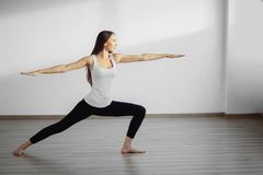 Young woman wearing white tank top working out, doing yoga exercise. Young woman wearing white tank top doing yoga exercise. Standing in Warrior one pose Stock Image