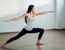 Young woman wearing white tank top working out, doing yoga exercise. Young woman wearing white tank top doing yoga exercise. Standing in Warrior one pose Royalty Free Stock Images